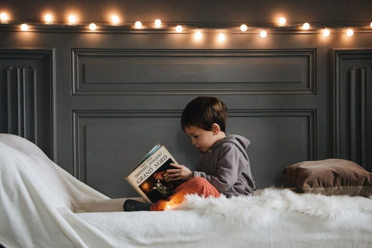 A kid reading a book in their soundproof bedroom